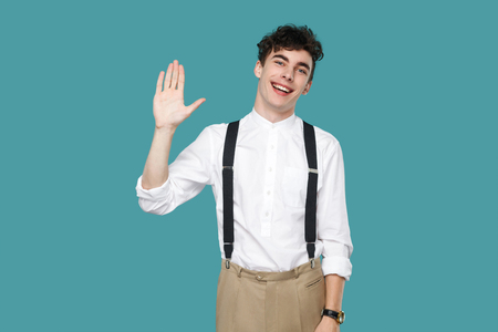 Happy excited man toothy smile and greeting. Portrait of handsome hipster curly young businessman in classic casual white shirt and suspender standing. indoor studio shot isolated on blue background.