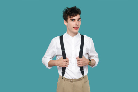 happy man toothy smile, standing and looking at camera. Portrait of handsome hipster curly young man in classic casual white shirt and suspender. indoor studio shot isolated on blue background.