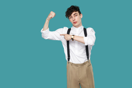 Proud man pointing at his biceps and looking at camera. Portrait of handsome hipster curly young businessman in classic casual white shirt and suspender. indoor studio shot isolated on blue background