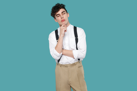 thoughtful man, touching his chin and thinking what to do. Portrait of handsome hipster curly young businessman in classic casual white shirt and suspender. studio shot isolated on blue background.