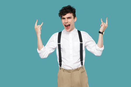 Man screaming and showing rock sign gesture. Portrait of handsome hipster curly young businessman in classic casual white shirt and suspender standing. indoor studio shot isolated on blue background.