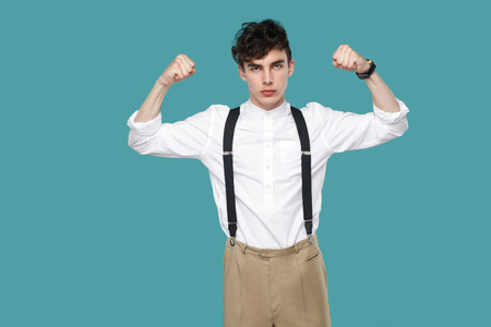Strong proud bossy man looking at camera. Portrait of handsome hipster curly young businessman in classic casual white shirt and suspender standing. indoor studio shot isolated on blue background.