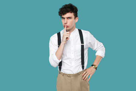 Serious man showing silent sign and looking at camera. Portrait of handsome hipster curly young businessman in classic casual white shirt, suspender standing. studio shot isolated on blue background.