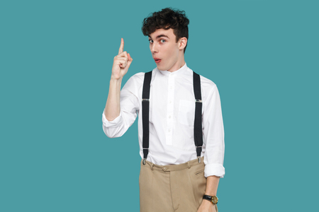Amazed suprised man with idea looking at camera. Portrait of handsome hipster curly young businessman in classic casual white shirt, suspender standing. indoor studio shot isolated on blue background.