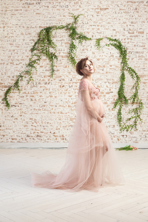 Full length portrait of sensual cheerful beautiful pregnant young woman in pink dress standing and holding with love her belly. Last months of pregnancy, studio shot, isolated, indoor, brick wall