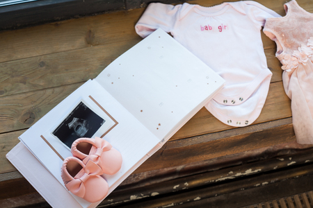 Baby girl pink dress clothes with newborn book album, body and little shoes and ultrasound scanning fetal photo on window wood sill background.