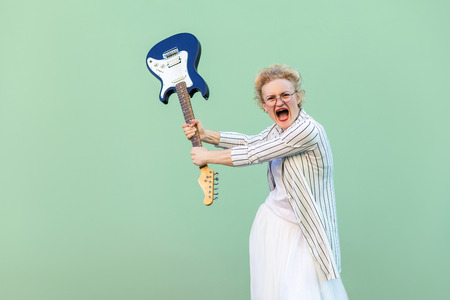 Portrait of angry young blonde woman in white striped blouse with eyeglasses standing, holding electric guitar looking, screaming and attacking. indoor studio shot isolated on light green background.