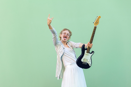Portrait of young blonde woman in white shirt, skirt, and striped blouse and electric guitar standing with rock sign tongue out and looking at camera. studio shot isolated on light green background. Imagens