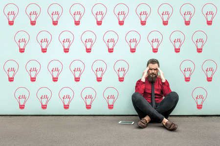 Try to find idea or problem solving. Young thoughtful bearded business man in red shirt sitting on floor and thinking what to do. drawed bulb lamp on wall. indoor studio shot on light blue background.