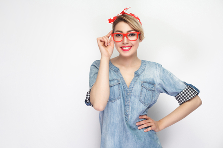 Portrait of beautiful young woman in casual blue denim shirt with makeup and red headband and glasses standing and looking at camera with toothy smile. indoor studio shot, isolated on white background
