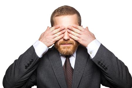 Nahaufnahmeporträt des gutaussehenden Geschäftsmannes mit Gesichtsbart im schwarzen Anzug, der steht und seine Augen schließt und nicht schauen möchte. Indoor-Studioaufnahme isoliert auf weißem Hintergrund.