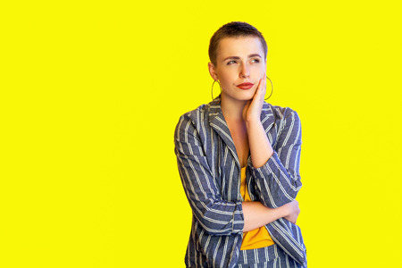 Portrait of thoughtful young short hair fancy casual stylish woman in yellow shirt and striped suit standing touching her face and thinking what to do. indoor studio shot isolated on yellow background