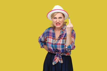 Portrait of angry modern stylish mature woman in casual style with hat and eyeglasses standing with middle finger fuck sign and looking at camera. indoor studio shot isolated on yellow background. Imagens