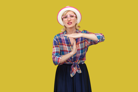 I need more time. Portrait of hopeful modern stylish mature woman in casual style with hat and eyeglasses standing with time gesture and hope to make timeout. studio shot isolated on yellow background
