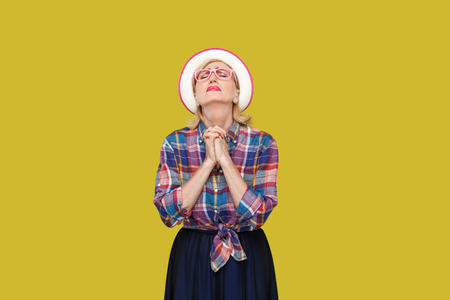 Oh my God please help me. Portrait of hopeful modern stylish mature woman in casual style with hat, eyeglasses standing with closed eyes and praying. indoor studio shot isolated on yellow background.