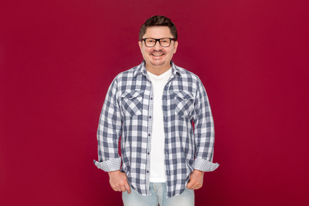 Portrait of happy satisfied handsome middle aged business man in casual checkered shirt and eyeglasses standing and looking at camera with toothy smile. studio shot, isolated on dark red background. 免版税图像