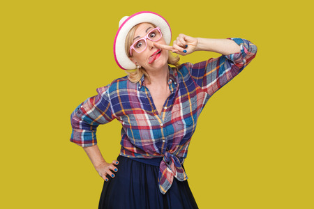 Portrait of funny crazy modern stylish mature woman in casual style with hat and eyeglasses standing with finger drilling nose and tongue out looking. indoor studio shot isolated on yellow background.