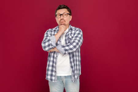 Portrait of thoughtful handsome middle aged business man in casual checkered shirt and eyeglasses standing, looking away and thinking what to do. indoor studio shot, isolated on dark red background.