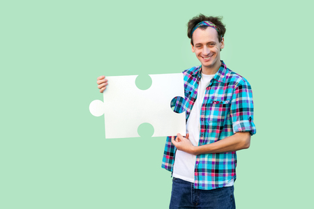 Happy handsome young man in checkered shirt standing and holding large piece of puzzle, looking at camera with toothy smile. Indoor, isolated, copy space, green background, studio shot
