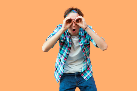 Portrait of surprised young man in casual blue checkered shirt and headband standing with binoculars hands gesture on eyes, looking with shocked face. indoor studio shot, isolated on orange background Imagens