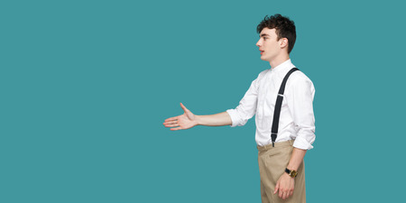 Profile side view portrait of happy handsome curly young businessman in classic casual white shirt standing and giving hand to greeting or handshake. indoor studio shot isolated on blue background. 免版税图像