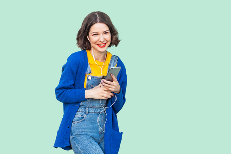 Portrait of beautiful cheerful young adult woman in hipster wear in denim overalls standing, holding phone and listening favourite music with handsets. Studio shot, green background, looking at camera