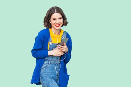 Retrato de hermosa mujer adulta joven alegre en ropa hipster en overoles de mezclilla de pie, sosteniendo el teléfono y escuchando música favorita con teléfonos. Foto de estudio, fondo verde, mirando a la cámara
