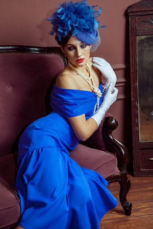 Old Fashioned retro great britain style photography. Beautiful young caucasian model in blue dress and fashion makeup and hat posing sitting on the artificial sofa and looking into the distance. Banco de Imagens - 121953919