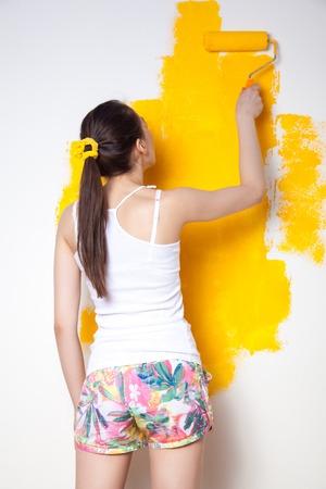 Bella giovane modella caucasica in pantaloncini colorati e camicia bianca e posa tenendo in mano un bilanciere, dipingendo il muro e guardando la telecamera. Colpo dello studio.