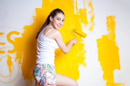Beautiful young caucasian model in coloured shorts and white shirt and posing holding outrigger in her hands, painting the wall and looking at camera. Studio shot. Stockfoto