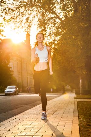 junges schönes glückliches und Läufermädchen mit schönem Körper im herbstlichen farbigen Park. mit sonne auf hintergrundbeleuchtung schaut mit glück in die kamera und lächelt mit weißem sportanzug. Standard-Bild