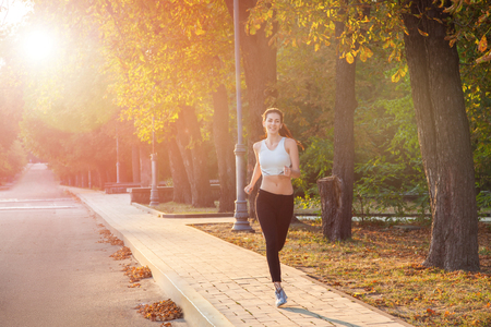junges schönes glückliches und Läufermädchen mit schönem Körper im herbstlichen farbigen Park. mit sonne auf hintergrundbeleuchtung schaut mit glück in die kamera und lächelt mit weißem sportanzug.