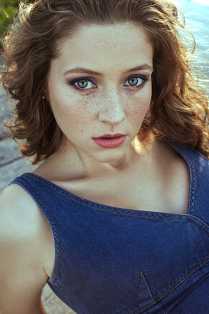 Beautiful young fashion model with freckles on her face and denim blue dress and fashion makeup and hairstyle is lying down on pier, posing and looking at camera.