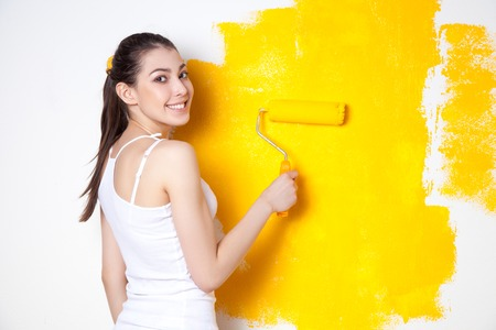 Beautiful young caucasian model in coloured shorts and white shirt and posing holding outrigger in her hands, painting the wall and looking at camera. Studio shot. Imagens
