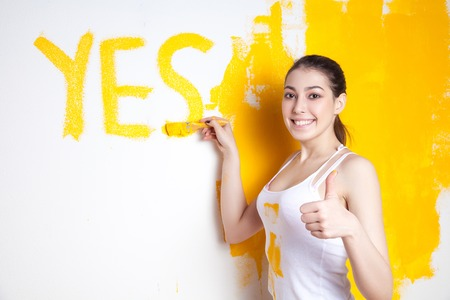 Beautiful young caucasian model in coloured shorts and white shirt and posing holding outrigger in her hands wrote yes on wall and shows her thumb, painting the wall and looking at camera. Studio shot. Stock Photo