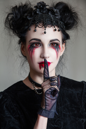 Young beautiful gothic woman with white skin and red lips with bloody drops wearing black collar with spikes. Red smokey eyes. Halloween makeup.