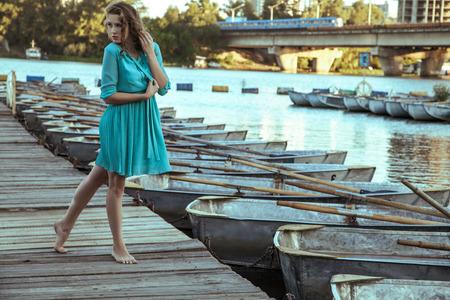 Piękna młoda modelka w turkusowej sukience i makijażu i fryzurze jest pozowanie na molo, pozowanie i patrząc w dal na drewnianej drodze. Zdjęcie Seryjne