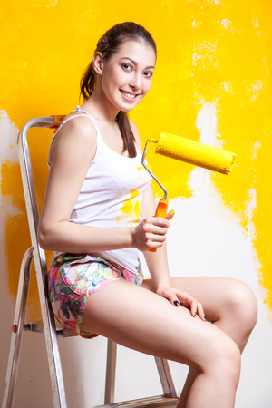 Beautiful young caucasian model in coloured shorts and white shirt and posing holding outrigger in her hands, painting the wall and looking at camera. Studio shot. Stock Photo