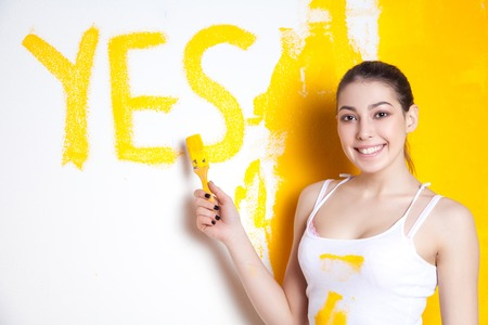 Beautiful young caucasian model in coloured shorts and white shirt and posing holding outrigger in her hands wrote Yes on wall, painting the wall and looking at camera. Studio shot. Stock Photo