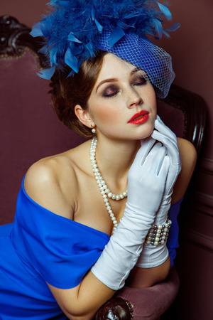 Old Fashioned retro great britain style photography. Beautiful young caucasian model in blue dress and fashion makeup and hat posing sitting on the artificial sofa and looking into the distance.
