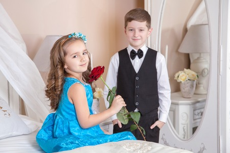 Beautiful young prince in tuxedo suit and princess holding rose in blue dress and fashion band posing sitting on the bed in bright room and looking into the distance. Love story. Studio shot.