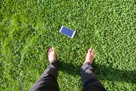 the man find mobile phone on grass. top view of human foot and mobile phone on grass. Stock Photo