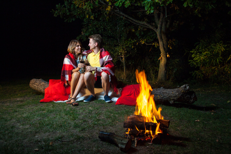 Young happy loving couple sitting on log near the fire covered with plaid holding wine, drinking and enjoy their romantic night. looking at each other and smiling. Banco de Imagens