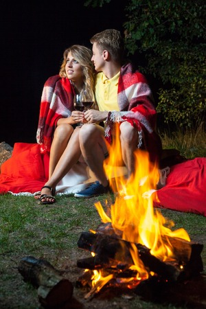 Young happy loving couple sitting on log near the fire covered with plaid holding wine, drinking and enjoy their romantic night.