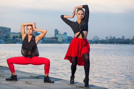 Two young beautiful twin sisters are dancing waacking dance in the city background near river. showing the different style and pose of modern dance with black and red dress near water on summer time.