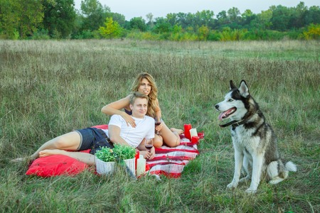 Beautiful young happy loving couple on picnic lying down on plaid with their dog  in field on sunny summer day enjoying, holding and drinking wine and resting. looking at their dog and smiling.