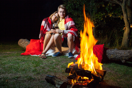 Young happy loving couple sitting on log near the fire covered with plaid holding wine, drinking and enjoy their romantic night. hugging and relaxing together.