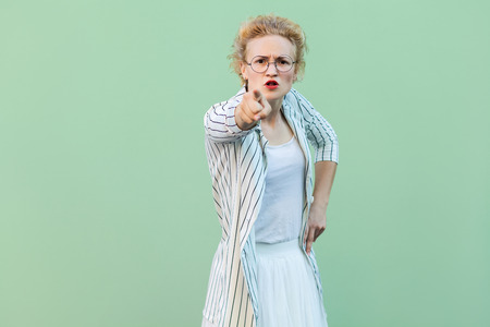 Hey you. Portrait of serious young blonde woman in white shirt, skirt, and striped blouse and eyeglasses standing, looking and pointing at camera. indoor studio shot isolated on light green background 写真素材