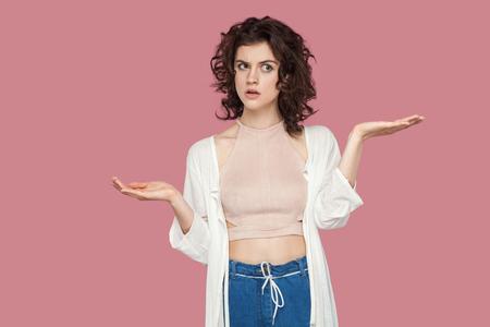 ¿Izquierda o derecha? Retrato de mujer joven morena hermosa dudosa con peinado rizado en estilo casual de pie, brazos levantados y confundido para elegir. tiro del estudio de interior aislado en fondo rosado. Foto de archivo