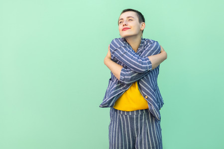 Portrait of happy handsome beautiful short hair young stylish woman in casual striped suit standing hugging herself with closed eyes and proud. indoor studio shot isolated on light green background. Stok Fotoğraf